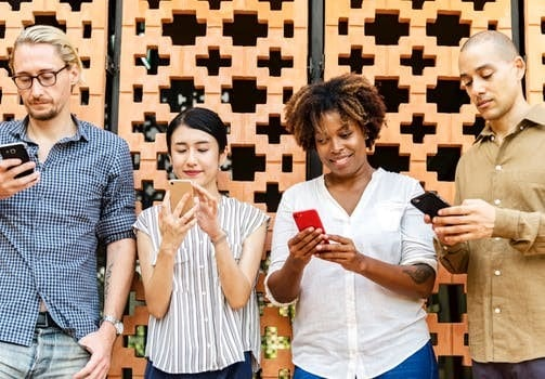 4 people holding mobile phones.